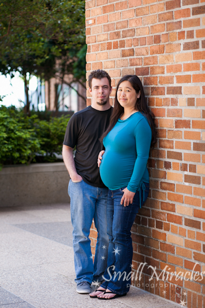 Pregnant couple with brick wall background
