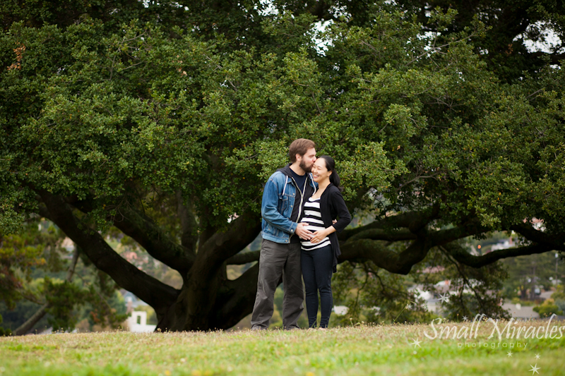 pregnant woman and husband in front of Oak Tree