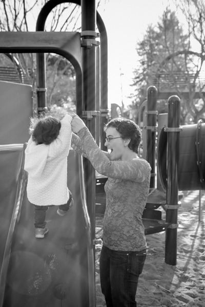 mom holding daughter's hands going up slide at playground