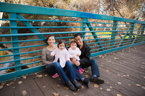 twin girls sitting with parents on scenic bridge in mountain view during family photo session