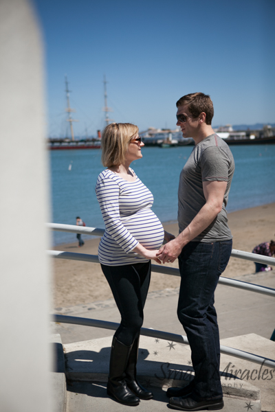 pregnant woman and husband in front of boat