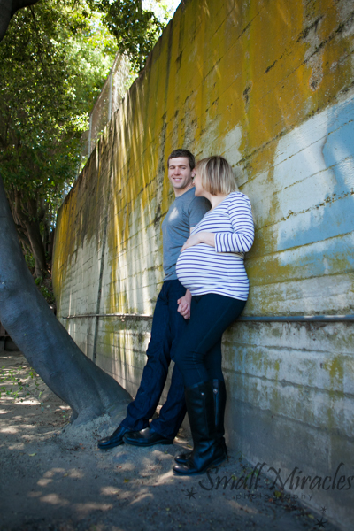 pregnat woman and husband in front of painted wall.