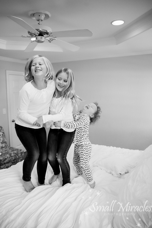 two sister jumping on the bed with little brother
