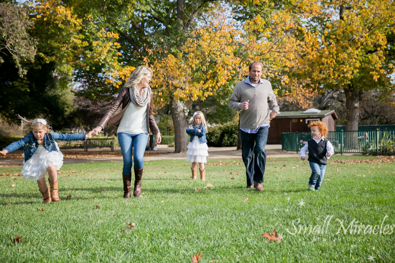 family photography of a family racing across grass with pouty girl