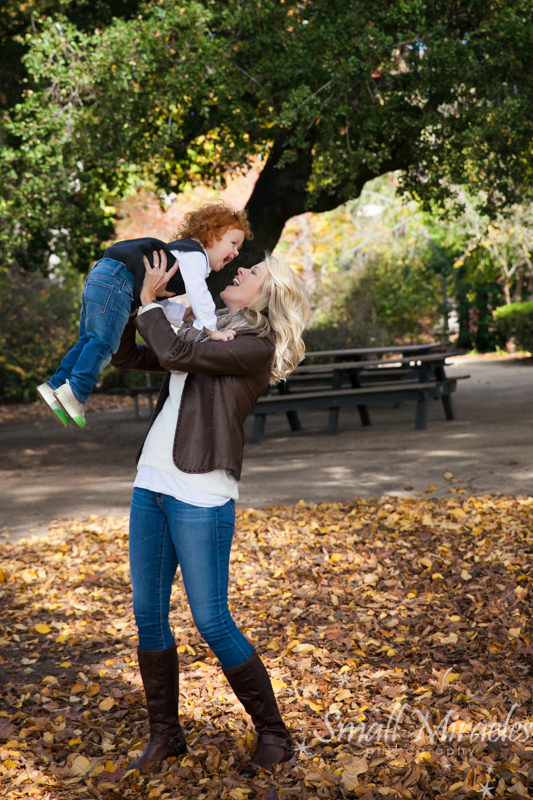 family photography of mom holding boy up in fall loacation