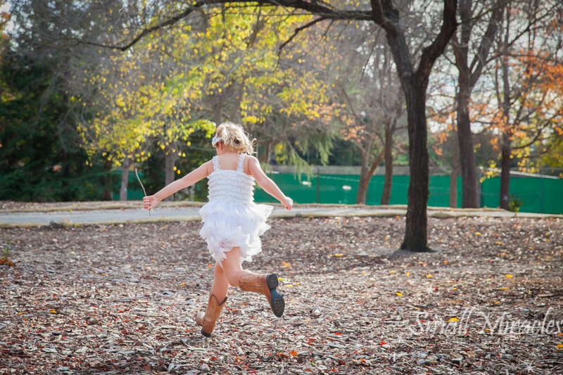 girl running in fall leaves in frilly dress and cowboy boots