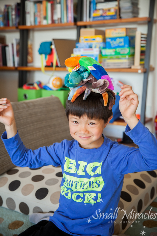 young boy with stuffed animals on his head