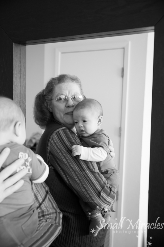 grandma holding little baby looking in mirror