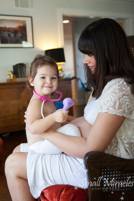 toddler checking mommy's baby bump with toy stethoscope
