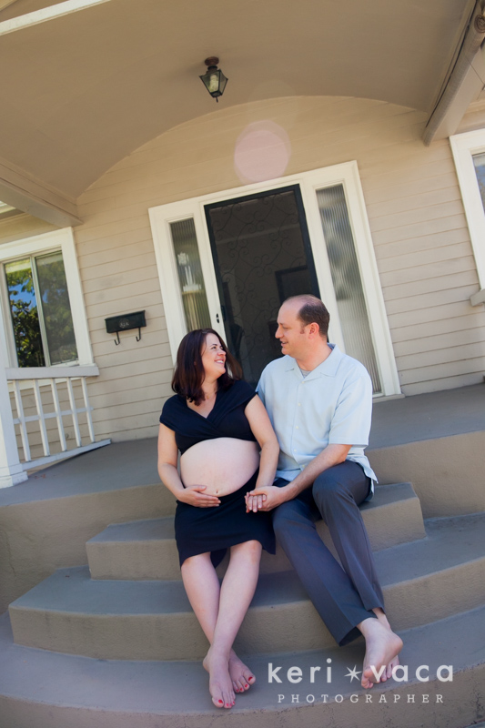 pregnant women and husband sitting on steps in front of her home with sunflare