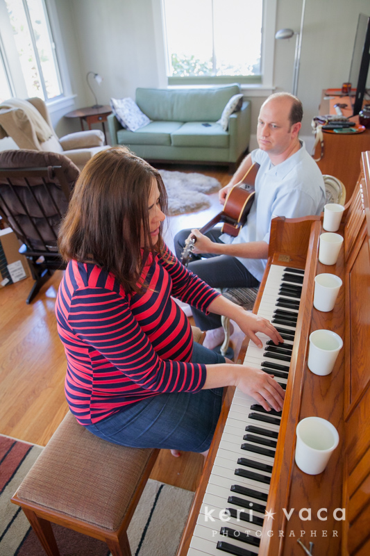 pregnant women playing the piano while husband plays the guitar during maternity photo shoot