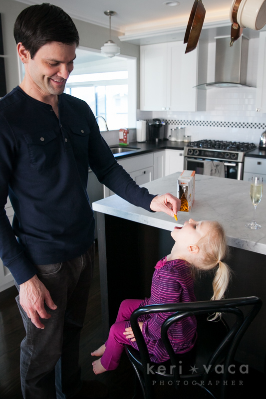 Dad feeding daughter Goldfish crackers during family photo session