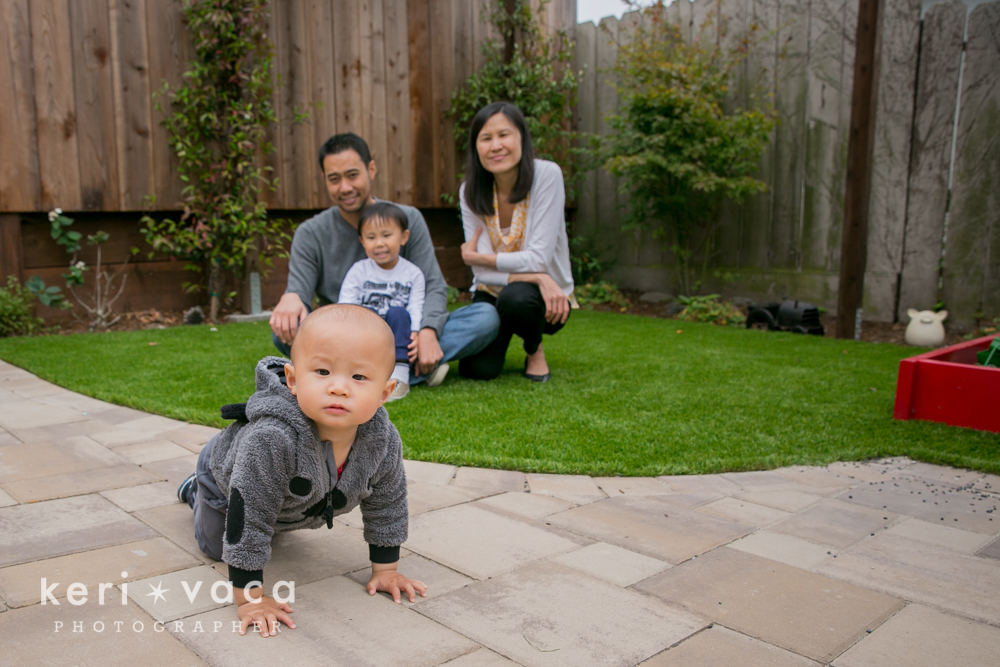 baby crawling away from family in backyard during family photos session