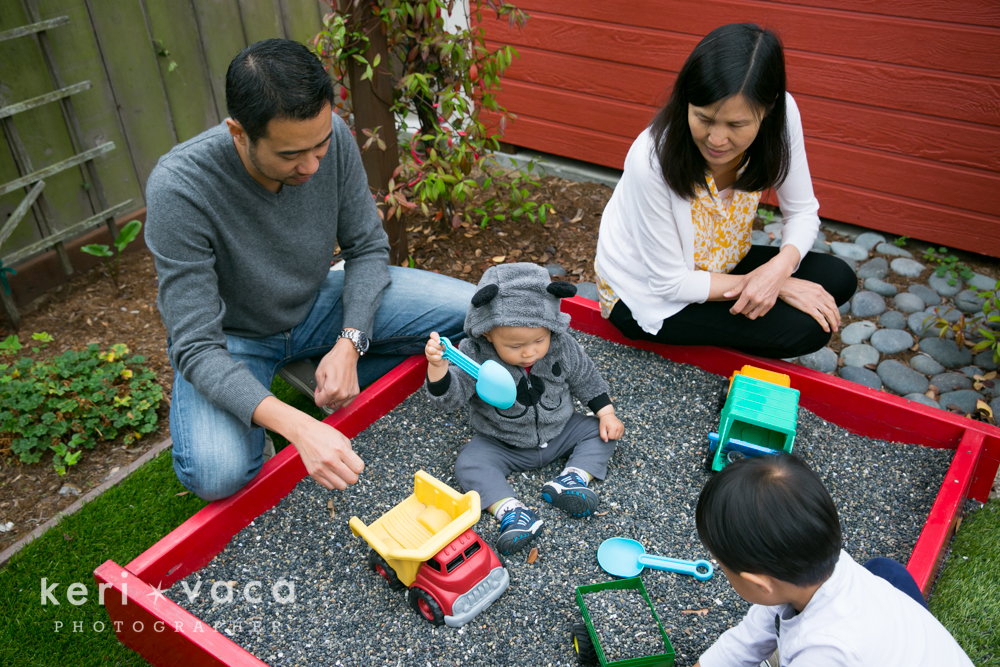 baby boy playing in backyard sand box during lifestyle photo shoot