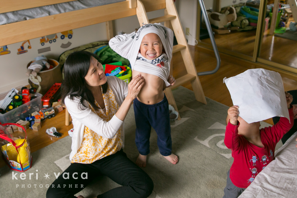 silly toddler pulling shirt over his head during family photography lifestyle photo session