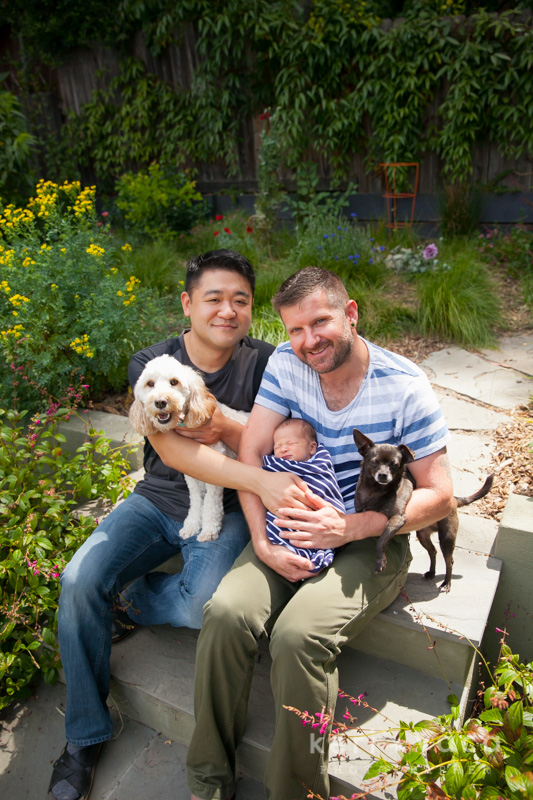 two dads, two dogs and their newborn baby boy in oakland backyard