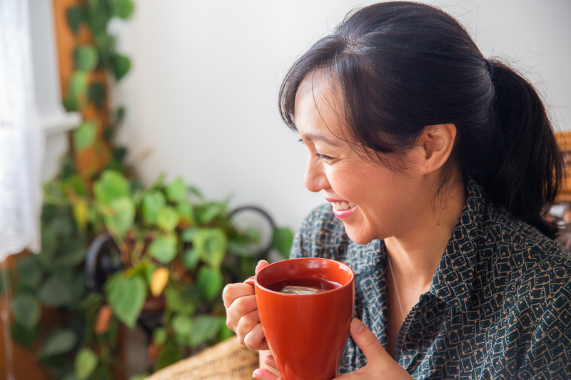 women drinking herbal tea in her office- business portrait